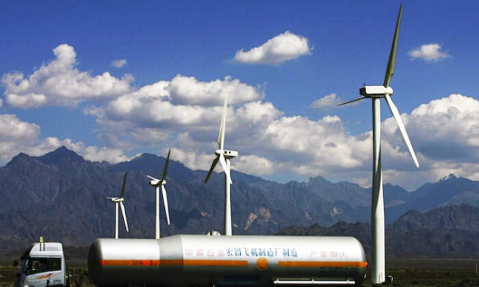An oil truck driving past wind turbines at the Dafancheng Wind Power Plant, the largest of its kind in Aisa, in 2007 in Dafancheng of Xinjiang Uygur Autonomous Region, China.  (China Photos/Getty Images)