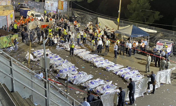 Israeli security officials and rescuers stand around the bodies of victims who died during Lag Baomer celebrations at Mt. Meron in northern Israel, on April 30, 2021. (Ishay Jerusalemite/Behadrei Haredim via AP)