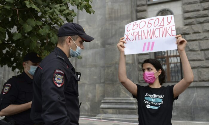 """Police detain a journalist with a poster reading """"Journalism Freedom"""" during individual pickets in Moscow on Aug. 21, 2021. (Denis Kaminev/AP Photo)"""