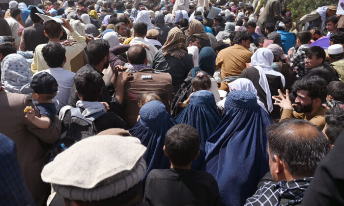 Afghans gather on a roadside near the military part of the airport in Kabul, hoping to flee from the country after the Taliban's military takeover of Afghanistan, in Kabul on Aug. 20, 2021. (Wakil Kohsar/AFP via Getty Images)