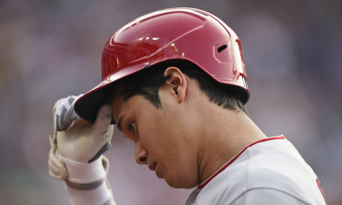Los Angeles Angels' Shohei Ohtani takes off his helmet as he walks back to the dugout after grounding out during the ninth inning of the team's baseball game against the Cleveland Indians in Cleveland on Aug. 21, 2021. The Indians won 5-1. (AP Photo/Tony Dejak)
