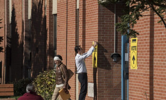 An Elections Canada volunteer tapes up signs at a polling station in Toronto on Oct. 19, 2015. (The Canadian Press/Aaron Vincent Elkaim)