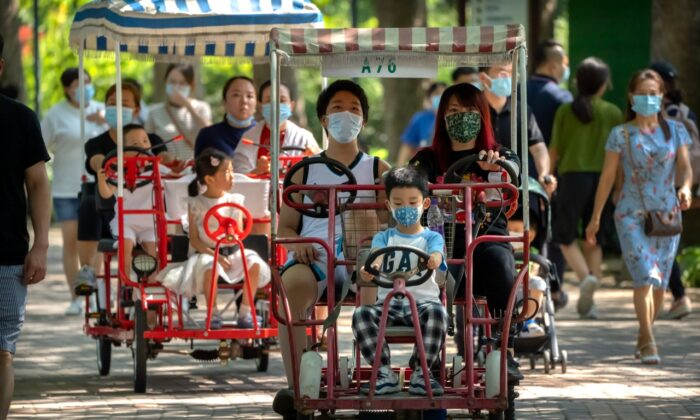 Adults and children ride pedal cycles at a public park in Beijing on Aug. 21, 2021. China will now allow couples to have a third child as the country seeks to hold off a demographic crisis that threatens its hopes of increased prosperity and global influence. (AP Photo/Mark Schiefelbein)