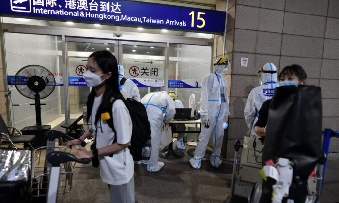Pudong airport workers in protective clothing help arriving international passengers as they prepare to board buses to be taken to quarantine hotels in Shanghai on Aug. 13, 2021. (Greg Baker/AFP)