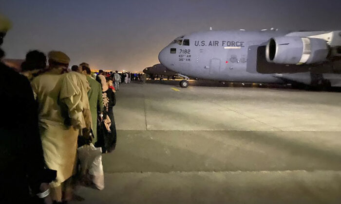 Afghan people queue up and board a U.S. military aircraft to leave Afghanistan, at the military airport in Kabul on Aug. 19, 2021. (Shakib Rahmani/AFP via Getty Images)