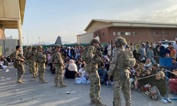 U.S. soldiers stand guard as Afghan people wait to board a U.S. military aircraft to leave Afghanistan, at the military airport in Kabul on Aug. 19, 2021. (Shakib Rahmani/AFP via Getty Images)