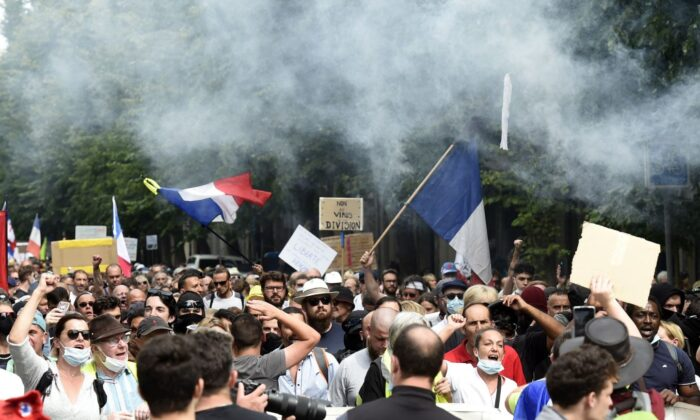 Protesters shout and wave flags during a national day of protest against the compulsory COVID-19 vaccination for certain workers and the mandatory use of the health pass called for by the French government in Lille, northern France, on Aug. 21, 2021. (Francois Lo Presti/AFP via Getty Images)