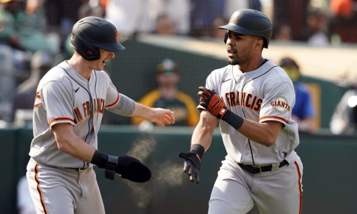 San Francisco Giants center fielder LaMonte Wade Jr (31) celebrates with right fielder Mike Yastrzemski (5) after hitting a home run during the ninth inning against the Oakland Athletics at RingCentral Coliseum, Oakland, Calif., on Aug 21, 2021. (Darren Yamashita/USA TODAY Sports via Reuters)