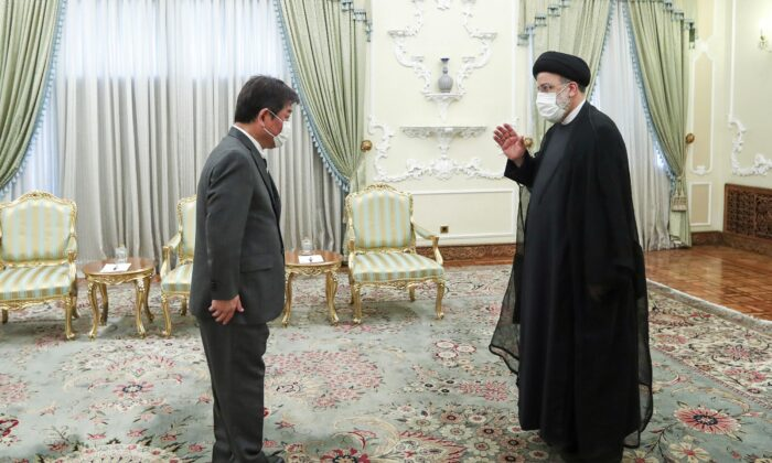 The Iranian President Ebrahim Raisi (R) welcomes Japanese Foreign Minister Toshimitsu Motegi for their meeting at the presidency office, in Tehran, Iran, on Aug. 22, 2021. (Iranian Presidency Office via AP)