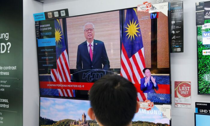 An electronic shop worker watches a speech by Malaysia's new Prime Minister Ismail Sabri Yaakob on television in Shah Alam, Malaysia, Sunday, Aug. 22, 2021. (Lai Seng Sin/AP Photo)