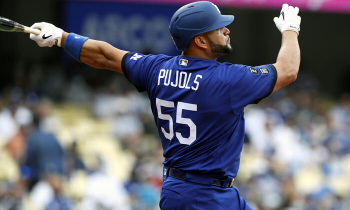 Los Angeles Dodgers' Albert Pujols follows through after hitting a solo home run against the New York Mets during the first inning of a baseball game in Los Angeles, Saturday, Aug. 21, 2021. (AP Photo/Alex Gallardo)