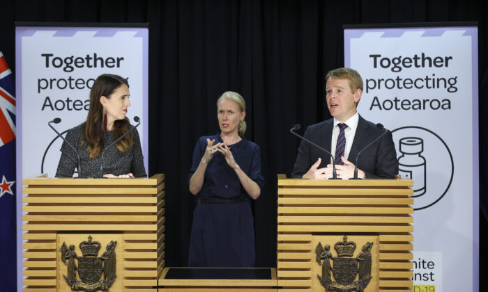 New Zealand's minister for COVID-19 Response, Chris Hipkins, speaks to media while Prime Minister Jacinda Ardern looks on during a press conference at Parliament in Wellington, New Zealand, on April 6, 2021. (Hagen Hopkins/Getty Images)