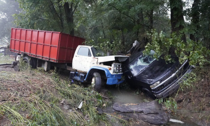 A truck and a car sit in a creek after they were washed away the day before in McEwen, Tenn., on Aug. 22, 2021. (Mark Humphrey/AP Photo)