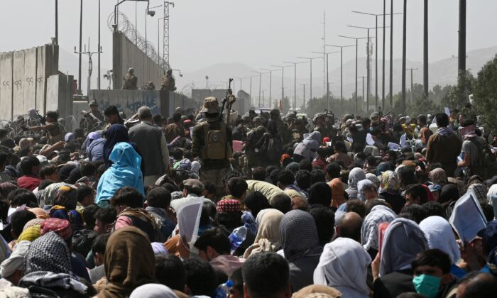 Afghans gather on a roadside near the military part of the airport in Kabul hoping to flee from the country after the Taliban's military takeover of Afghanistan on Aug. 20, 2021,. (Wakil Kohsar/AFP via Getty Images)