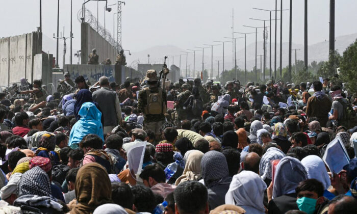 Afghans gather on a roadside near the military part of the airport in Kabul, Afghanistan on Aug. 20, 2021. (Photo by Wakil Kohsar/AFP via Getty Images)