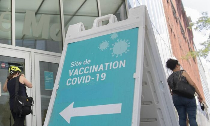 People are shown next to a COVID-19 vaccination sign in Montreal, on Aug. 21, 2021. (The Canadian Press/Graham Hughes)