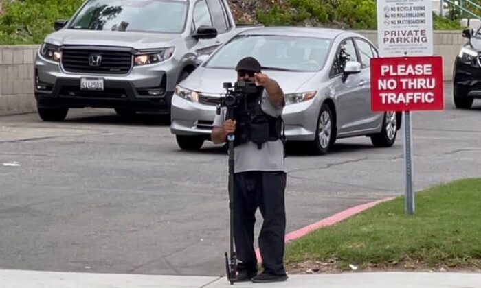 """A videographer stands with a camera """"auditing"""" traffic at a Yorba Linda church on Aug. 22, 2021. (Courtesy of Yorba Linda News You Can Use Facebook Group)"""