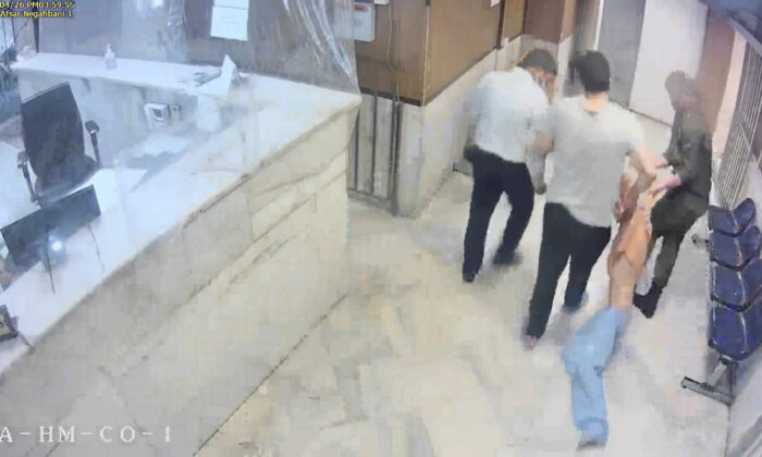 """In this undated frame grab taken from video shared with The Associated Press by a self-identified hacker group called """"The Justice of Ali,"""" guards drag an emaciated prisoner, at Evin prison in Tehran, Iran (The Justice of Ali via AP)"""