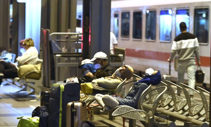 Passengers wait for their onward journey, which is delayed due to a strike by the train drivers' union GDL, at Cologne central station, Germany, on Aug. 23, 2021. (Roberto Pfeil/dpa via AP)