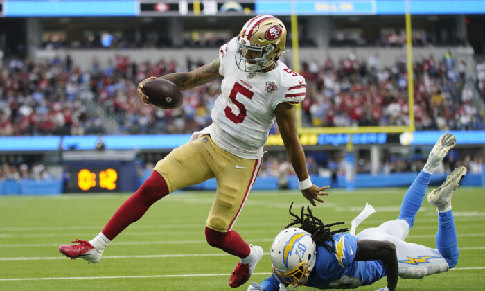 San Francisco 49ers quarterback Trey Lance (5) runs around Los Angeles Chargers defensive back Tevaughn Campbell (20) on a a failed two-point conversion attempt during the first half of a preseason NFL football game in Inglewood, Calif., on Aug. 22, 2021. (AP Photo/Ashley Landis)