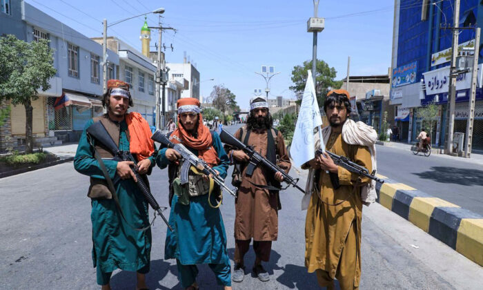 Taliban fighters stand guard along a road near the site of an Ashura procession which is held to mark the death of Imam Hussein, the grandson of Prophet Mohammad, along a road in Herat on Aug. 19, 2021, amid the Taliban's military takeover of Afghanistan. (Aref Karimi/AFP via Getty Images)