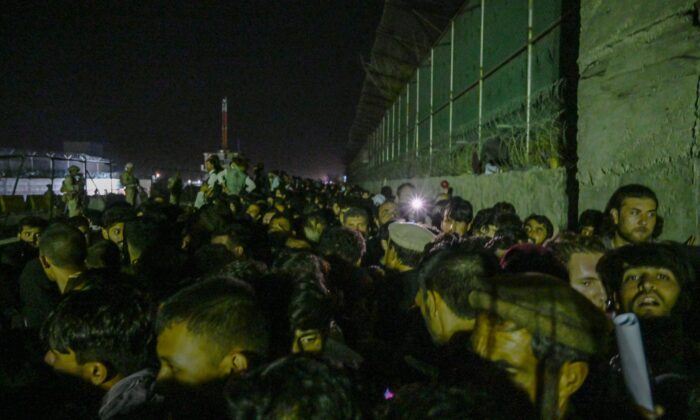 In this picture taken late at night Afghans wait outside the foreign military-controlled part of the airport in Kabul, hoping to flee the country following the Taliban's military takeover of Afghanistan, on Aug. 22, 2021. (Wakil Kohsar/AFP via Getty Images)