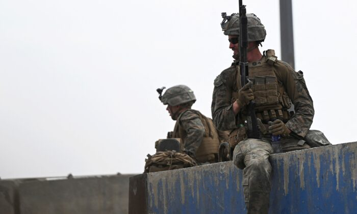 U.S. soldiers sit on a wall as Afghans gather on a roadside near the military part of the airport in Kabul on Aug. 20, 2021. (Wakil Kohsar/AFP)