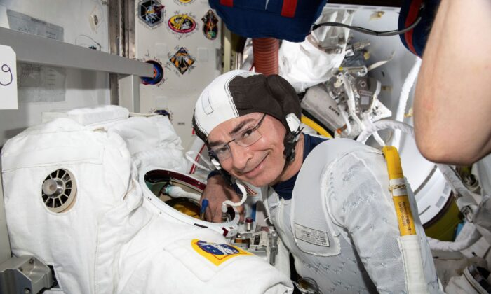 Astronaut and Expedition 65 Flight Engineer Mark Vande Hei inspects a spacesuit in preparation for a spacewalk at the International Space Station on Aug. 17, 2021. (NASA via AP)