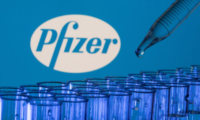 Test tubes are seen in front of  a displayed Pfizer logo in this illustration photo taken on May 21, 2021. (Reuters/Dado Ruvic/Illustration)