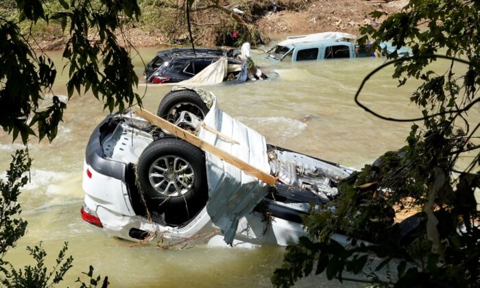 Vehicles come to rest in a stream in Waverly, Tenn., on Aug. 22, 2021. (Mark Humphrey/AP Photo)