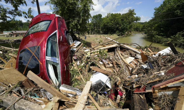 A car is among debris that washed up against a bridge over a stream in Waverly, Tenn., on Aug. 22, 2021. (Mark Humphrey/AP Photo)