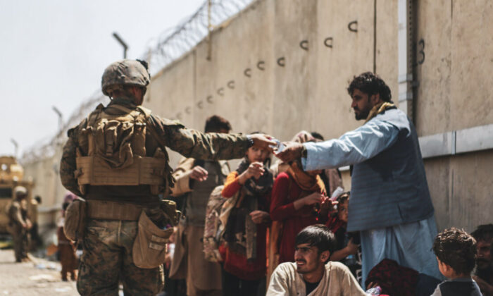 A Marine with the 24th Marine Expeditionary unit (MEU) passes out water to evacuees during the evacuation at Hamid Karzai International Airport during the evacuation in Kabul, Afghanistan, on Aug. 21, 2021. (Isaiah Campbell/U.S. Marine Corps via Getty Images)