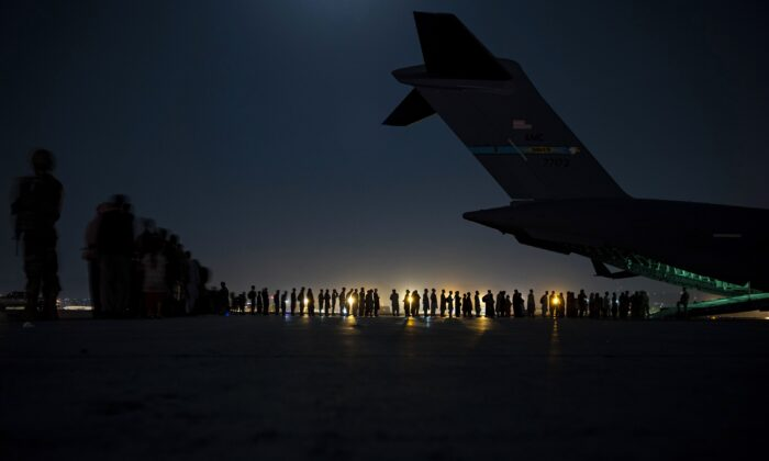 U.S. Air Force aircrew, assigned to the 816th Expeditionary Airlift Squadron, prepare to load qualified evacuees aboard a U.S. Air Force C-17 Globemaster III aircraft in support of the Afghanistan evacuation at Hamid Karzai International Airport, Kabul, Afghanistan on Aug. 21, 2021. (Senior Airman Taylor Crul/U.S. Air Force via AP)