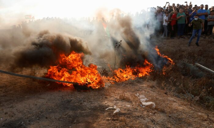 Protestors set fire on a tire near the fence of Gaza Strip border with Israel, during a protest marking the anniversary of a 1969 arson attack at Jerusalem's Al-Aqsa mosque by an Australian tourist later found to be mentally ill, east of Gaza City, on Aug. 21, 2021. (Adel Hana/AP Photo)