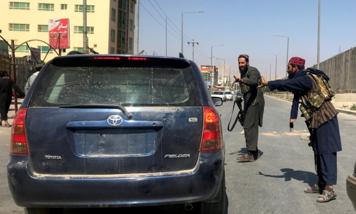 Taliban terrorists gesture as they check a vehicle on a street in Kabul, Afghanistan, on Aug. 16, 2021. (Stringer/Reuters)
