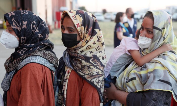 Afghan women queue upon their arrival aboard a second evacuation airplane, carrying Afghan collaborators and their families, that landed at the Torrejon de Ardoz air base, 30 km (18.6 miles) away from Madrid on Aug. 20, 2021. (Mariscal/ POOL/ AFP via Getty Images)