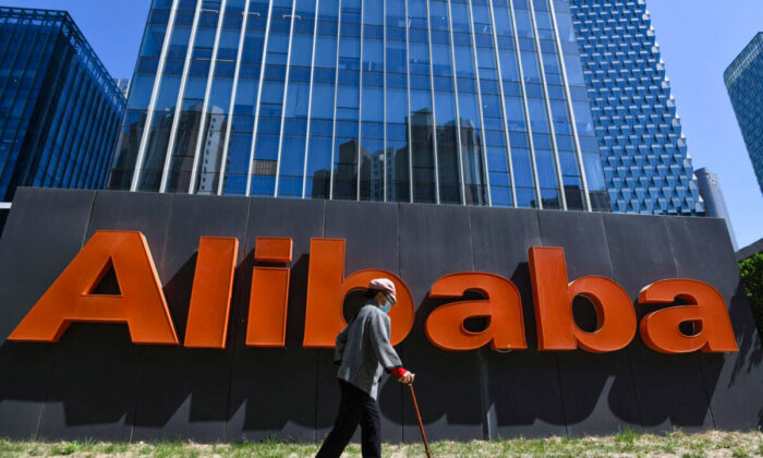 A woman walks past an Alibaba sign outside the company's office in Beijing, China, on April 13, 2021. (Greg Baker/AFP via Getty Images)