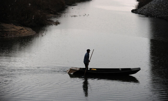 A Chinese fisherman sails on a tributary of the Yalu River between North Korea and China on Nov. 24, 2010. (Frederic J. Brown/AFP via Getty Images)