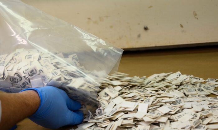 A Drug Enforcement Administration (DEA) chemist pours 2,500 packs of confirmed fentanyl onto a counter for testing at the DEA Northeast Regional Laboratory in New York on Oct. 8, 2019. (Don Emmert/AFP via Getty Images)