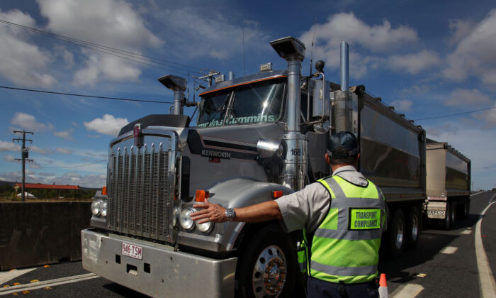 A Queensland Transport Inspector signals to a truck driver at the Queensland border in Wallangarra, Australia, on April 2, 2020.  (Lisa Maree Williams/Getty Images)