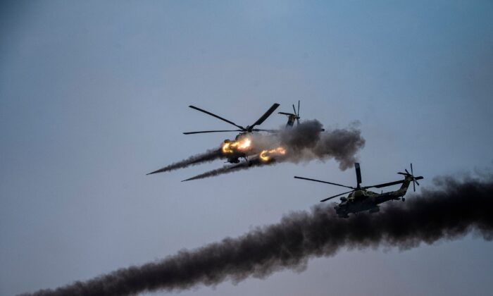 """Russian attack helicopters launch rockets during military exercises at the Kapustin Yar range in Astrakhan region, Southern Russia on Sept. 25, 2020 during the """"Caucasus-2020"""" military drills gathering China, Iran, Pakistan and Myanmar troops, along with ex-Soviet Armenia, Azerbaijan and Belarus. (Dimitar Dilkoff/AFP via Getty Images)"""