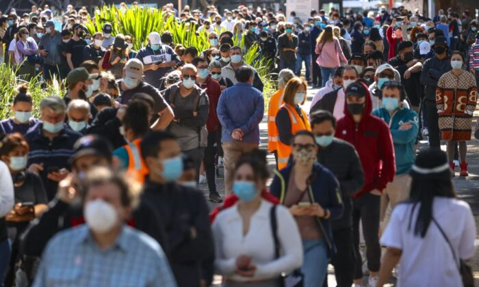 People wearing face masks stand in a line as they wait to be vaccinated at the Sydney Olympic Park Vaccination Centre at Homebush in Sydney, Australia, on Aug. 16, 2021. (David Gray/AFP via Getty Images)