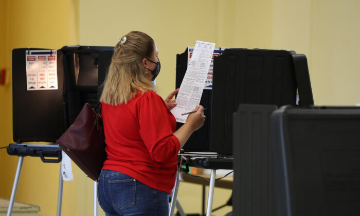 A voter reads her ballot while voting at the Legion Park polling place in Miami on Nov, 3, 2020.  (Joe Raedle/Getty Images)