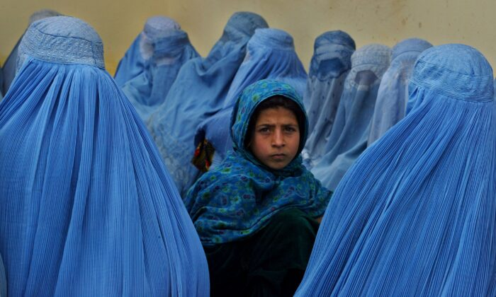Afghan women wait in line to be treated at the Kalakan health clinic in Kalakan, Afghanistan, on Feb. 23, 2003. (Paula Bronstein/Getty Images)