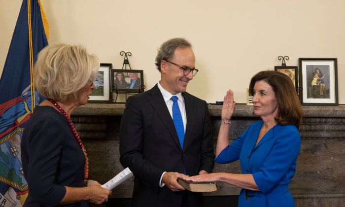 Kathy Hochul (R) is sworn-in as New York State's 57th Governor by Chief Judge Janet DiFiore (L) while First Gentleman Bill Hochul (C) holds the Bible, at the New York State Capitol, in New York, on Aug. 24. (Mike Groll/Office of Governor Kathy Hochul)