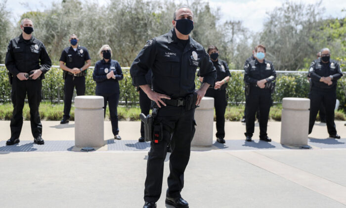Los Angeles Police Department officers wear face masks as they wait to salute healthcare workers as a fellow LAPD detective is released from Providence St. John's Health Center in Santa Monica, Calif., on April 17, 2020. (Mario Tama/Getty Images)