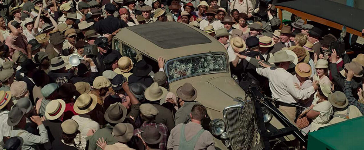 a crowd mobs a car in THE HIGHWAYMEN