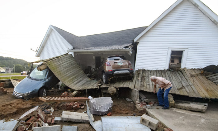 A man examines flood damage to his granddaughter's house in Waverly, Tenn., on Aug. 23, 2021. (AP Photo/John Amis)