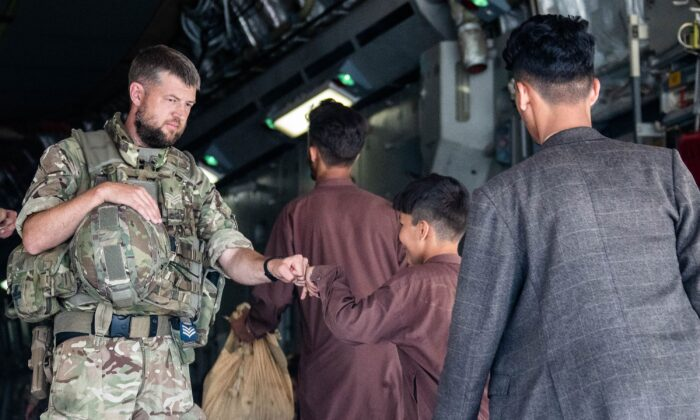 A member of the UK Armed Forces fist-bumping a child evacuee at Kabul airport in an undated file photo. (LPhot Ben Shread/MoD via PA)