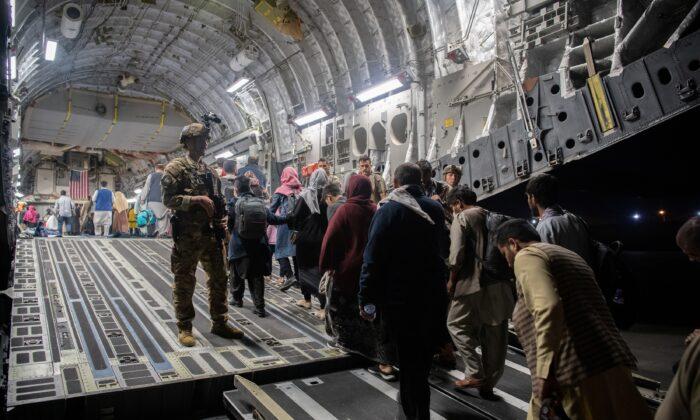 Afghans board a U.S. Air Force C-17 Globemaster III transport plane during an evacuation at Hamid Karzai International Airport, Afghanistan, on Aug. 22, 2021. (U.S. Air Force via Reuters)